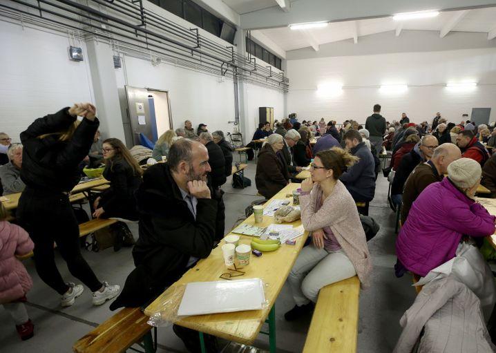 Menschen, die ihre Wohnungen wegen der Entschärfung einer Weltkriegsbombe verlassen mussten, warten in einer Halle der Mudra-Kaserne auf die Entschärfung der Bombe