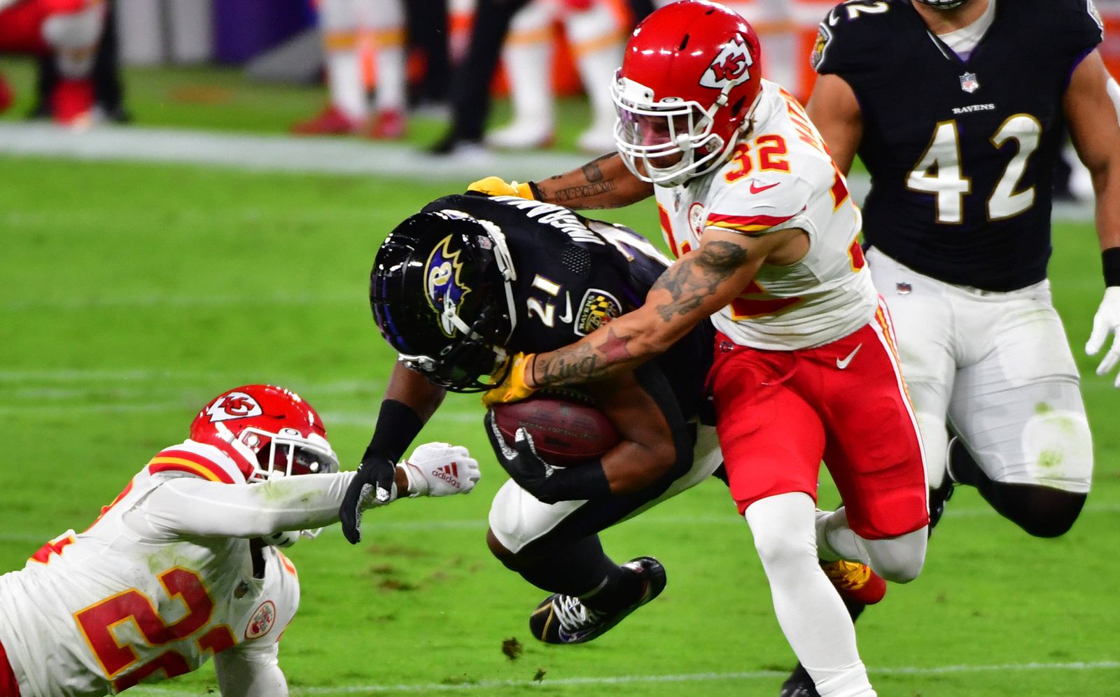 Baltimore Ravens running back Mark Ingram (21) is stopped by Kansas City Chiefs defenders Juan Thornhill (22) and Tyran