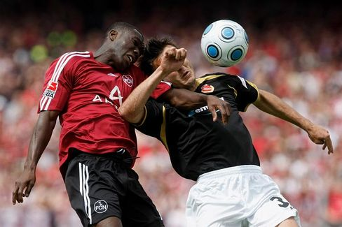 Isaac Boayke (l) of Nuernberg jumps for a header with Mario Cvitanovic of Energie Cottbus.