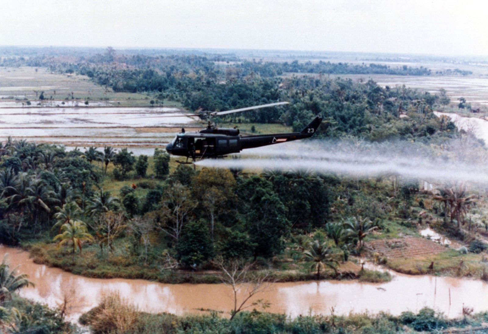 Vietnam: A US Huey helicopter spraying agent orange during Operation Ranch Hand, c. 1965