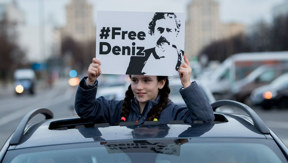 A girl in Berlin holds up a sign of the German journalist arrested in Turkey.