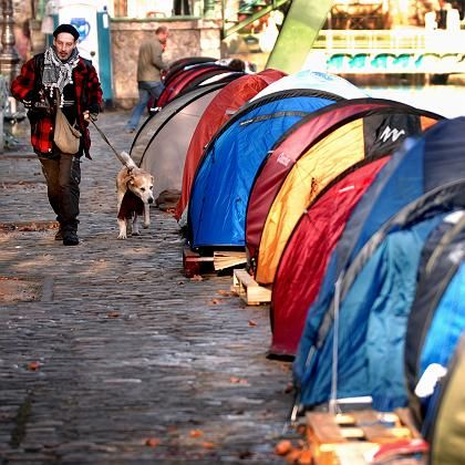 A man walks past a tent city for the homeless along the Canal Saint-Martin in Paris. The association Les Enfants de Don Quichotte set up temporary camping grounds in Paris and elsewhere to draw attention to the plight of the homeless.