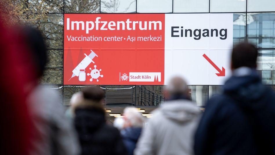 Menschen warten vor einem Impfzentrum in Köln