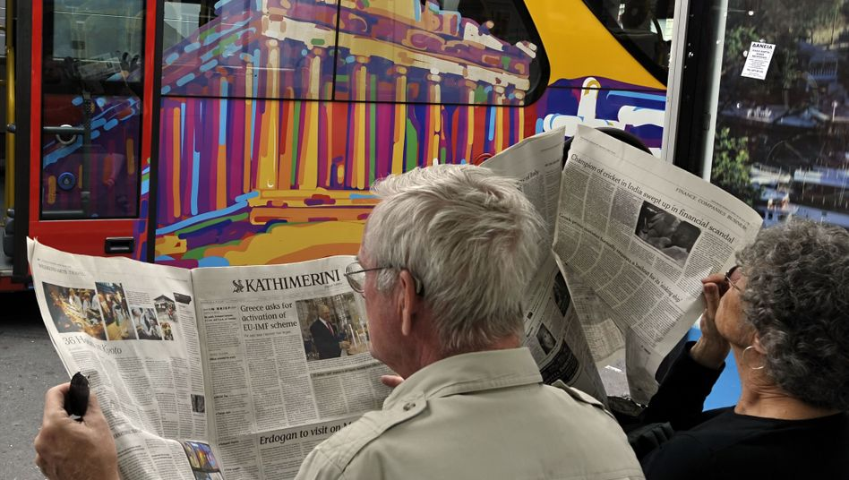 """Foreigners read newspapers in Athens: Germany's foreign minister has warned that the Greek financial crisis threatens to spread across the EU """"like the ebola virus."""""""