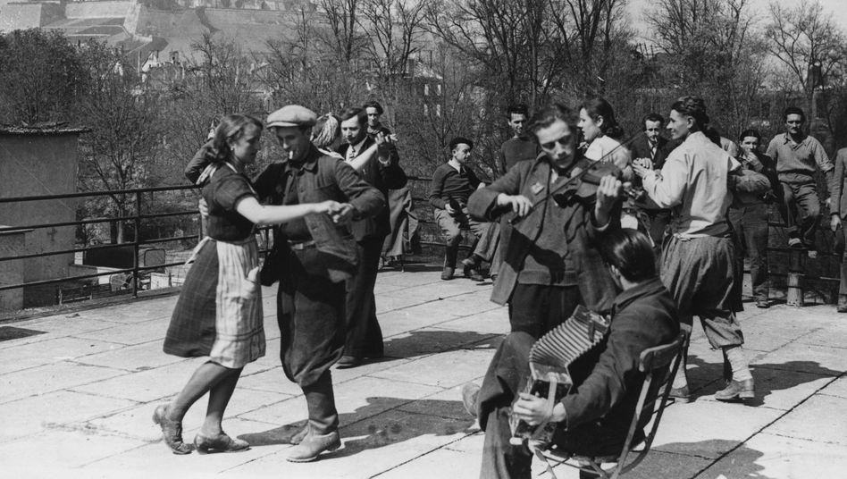 Ehemalige Zwangsarbeiter, 1945 von der 7. US-Armee befreit, tanzen auf dem Dach des »Dr.-Goebbels-Hauses« in Würzburg