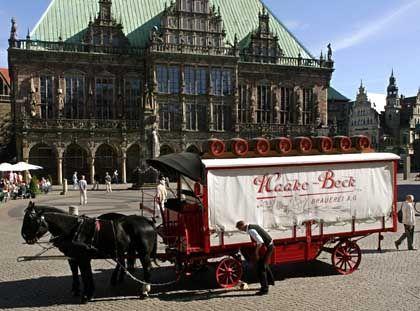 Brauerei vor dem Rathaus in Bremen: Seit Jahrzehnten gehört das mit Flaschen und Bierfässern beladene und von zwei Rappen gezogene Gespann zum Stadtbild der Hansestadt