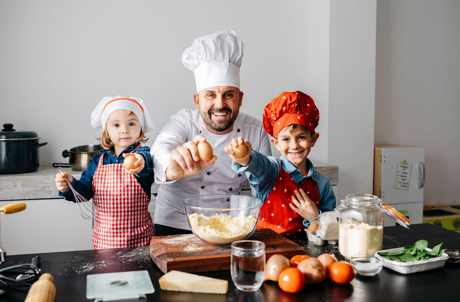 Portrait of father with two kids preparing dough in kitchen at home model released Symbolfoto property released JRFF0427