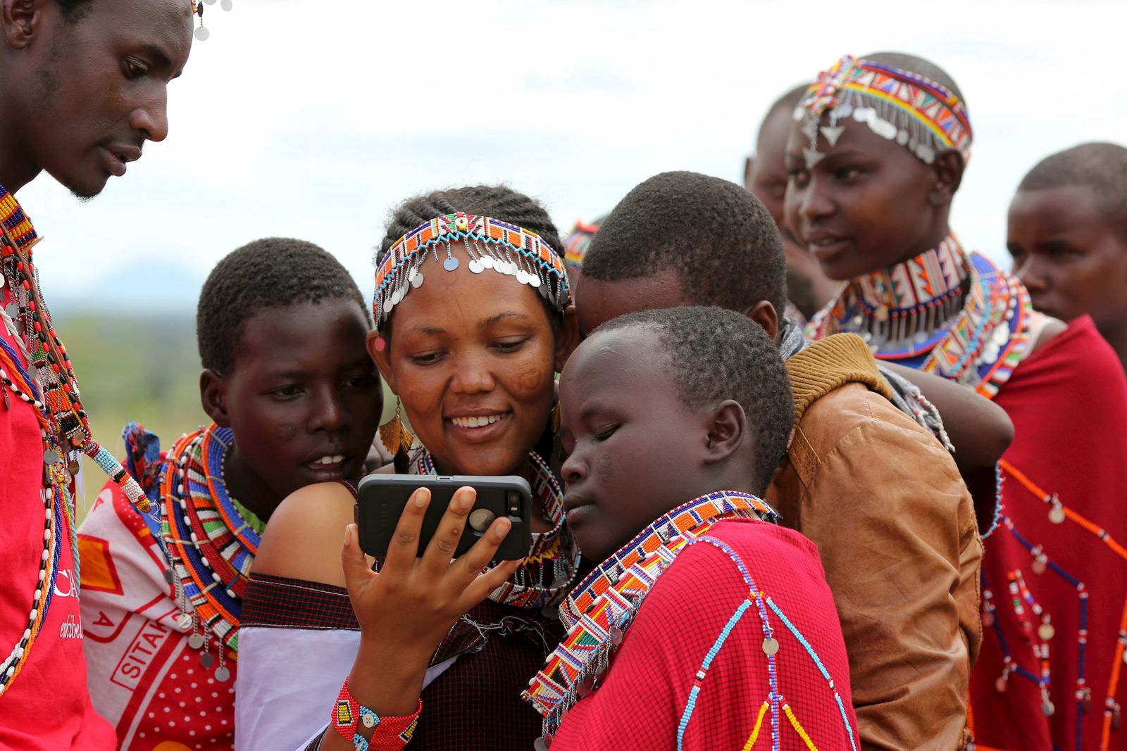 Maasai girls and a man watch a video on a mobile phone prior to the start of a social event advocating against harmful practices such as Female Genital Mutilation (FGM) at the Imbirikani Girls High School in Imbirikani, Kenya
