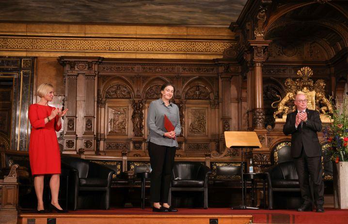 Die britische Chemikerin Clare Grey (M.) freut sich im Rathaus Hamburg über ihre Urkunde