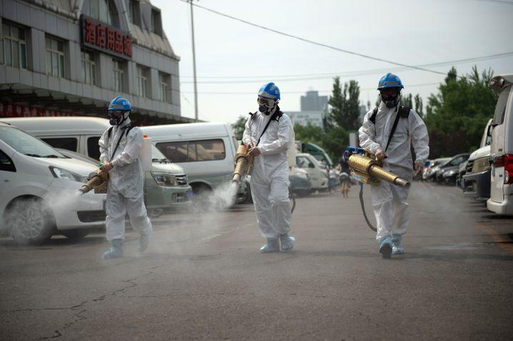 Sicherheitspersonal desinfiziert das Gelände des Yuegezhuang-Großmarkts in Peking