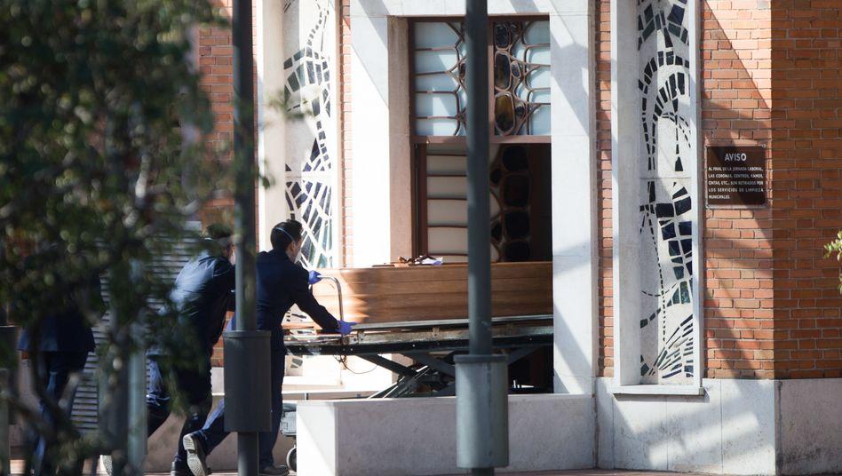 Mehr als 3000 Corona-Tote in Spanien: Arbeiter bringen einen Sarg in das städtische Bestattungsinstitut in Madrid