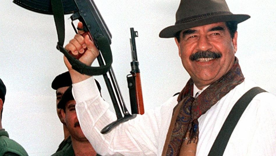 Saddam Hussein brandishing an AK 47 during a visit to villages in northern Iraq in 1998.