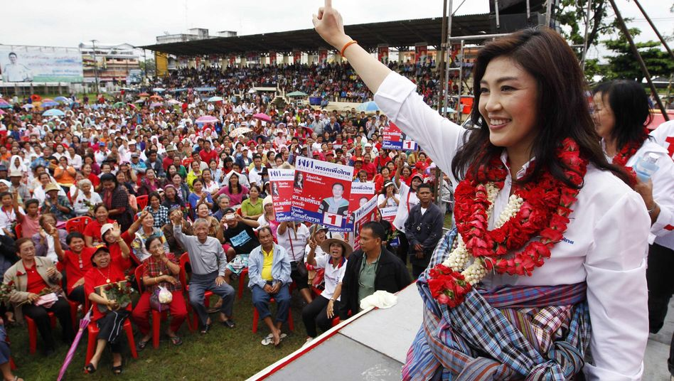 Yingluck Shinawatra, the sister of toppled former Thai premier Thaksin Shinawatra and the prime ministerial candidate for the country's biggest opposition Pheu Thai Party, greets her supporters.