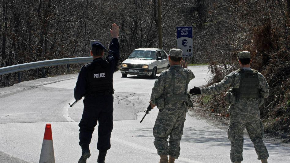 Weiterhin keine stabile Region: Kosovo-Polizist kontrolliert mit US-Soldaten ein Fahrzeug