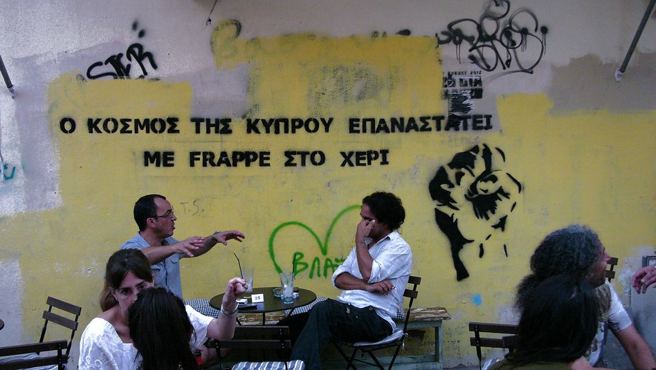 """People sit at a coffee shop as on a wall reading in Greek, """"The people in Cyprus make revolution with frappe in their hands"""" in Nicosia."""