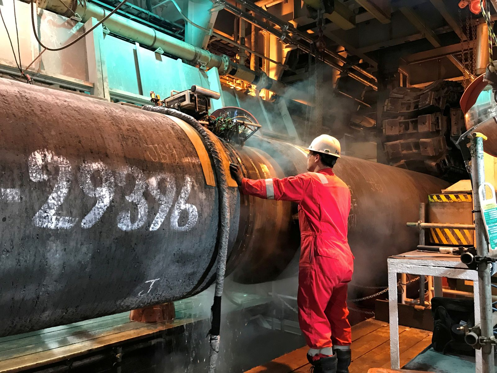 FILE PHOTO: A specialist works onboard the Allseas' deep sea pipe laying ship Solitaire to prepare a pipe for Nord Stream 2 pipeline in the Baltic Sea