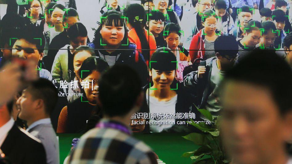 Passanten gehen in Peking an einem Bildschirm vorbei, auf dem eine Gesichtserkennung gezeigt wird.