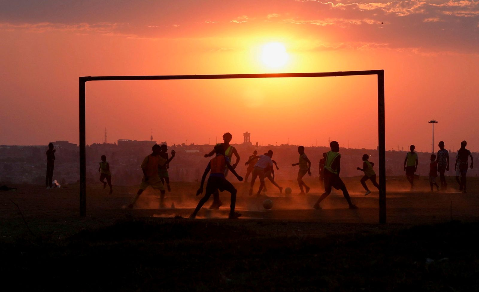 Locals play soccer on a dusty pitch in Soweto