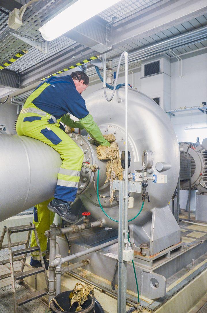 Ein Mitarbeiter der Berliner Wasserbetriebe entfern einen faserigen Zopf aus einer Abwasserpumpe
