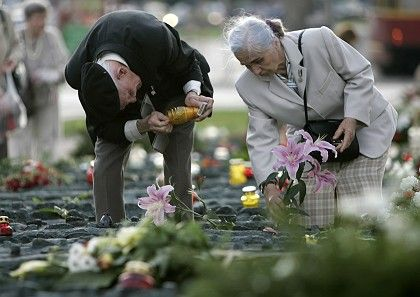 An elderly couple lights candles by the monument dedicated to the victims of Katyn, the Russian forest where thousands of Polish officers were executed in 1940.