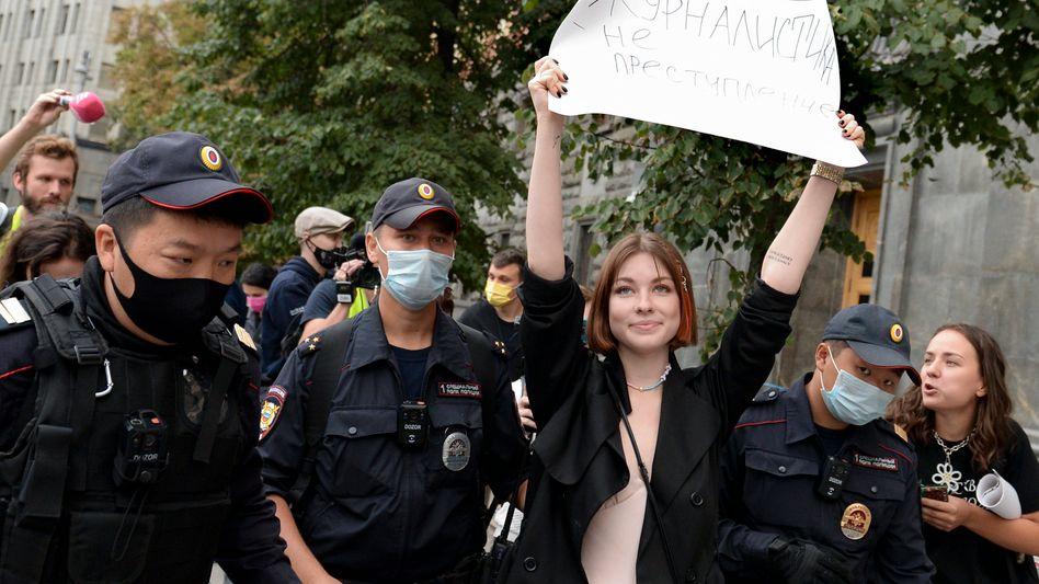Polizisten nehmen eine Demonstrantin in Moskau vor der FSB-Zentrale fest, sie hält ein Plakat mit der Aufschrift »Journalismus ist kein Verbrechen« hoch