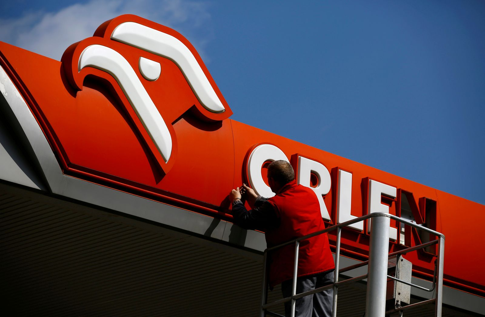 FILE PHOTO: A man fixes PKN Orlen logo, Poland's top oil refiner, at their petrol station in Warsaw