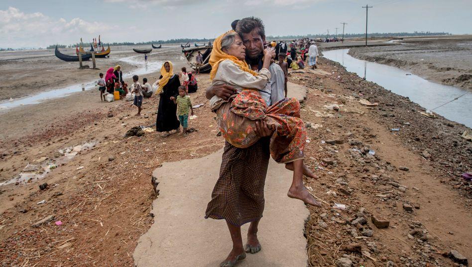 Ein Rohingya trägt seine Mutter auf der Flucht aus Myanmar nach Bangladesch