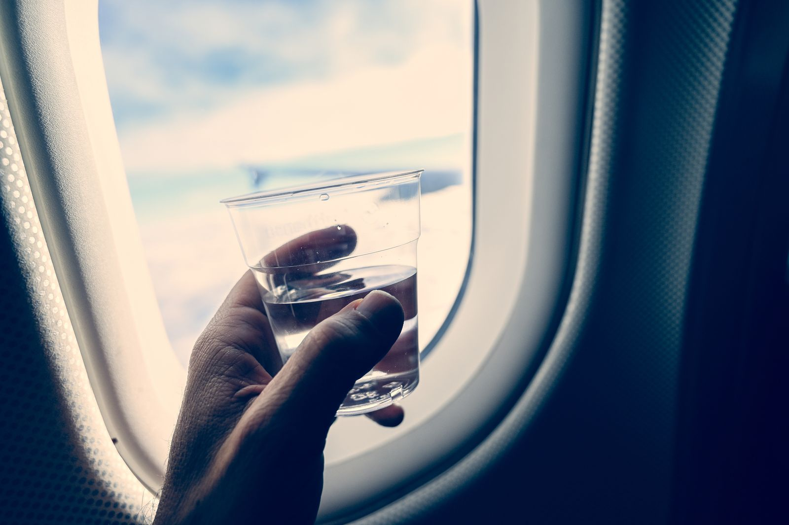 Man's hand holding a glass with transparent liquid (water or liquor). Inside an airplane.