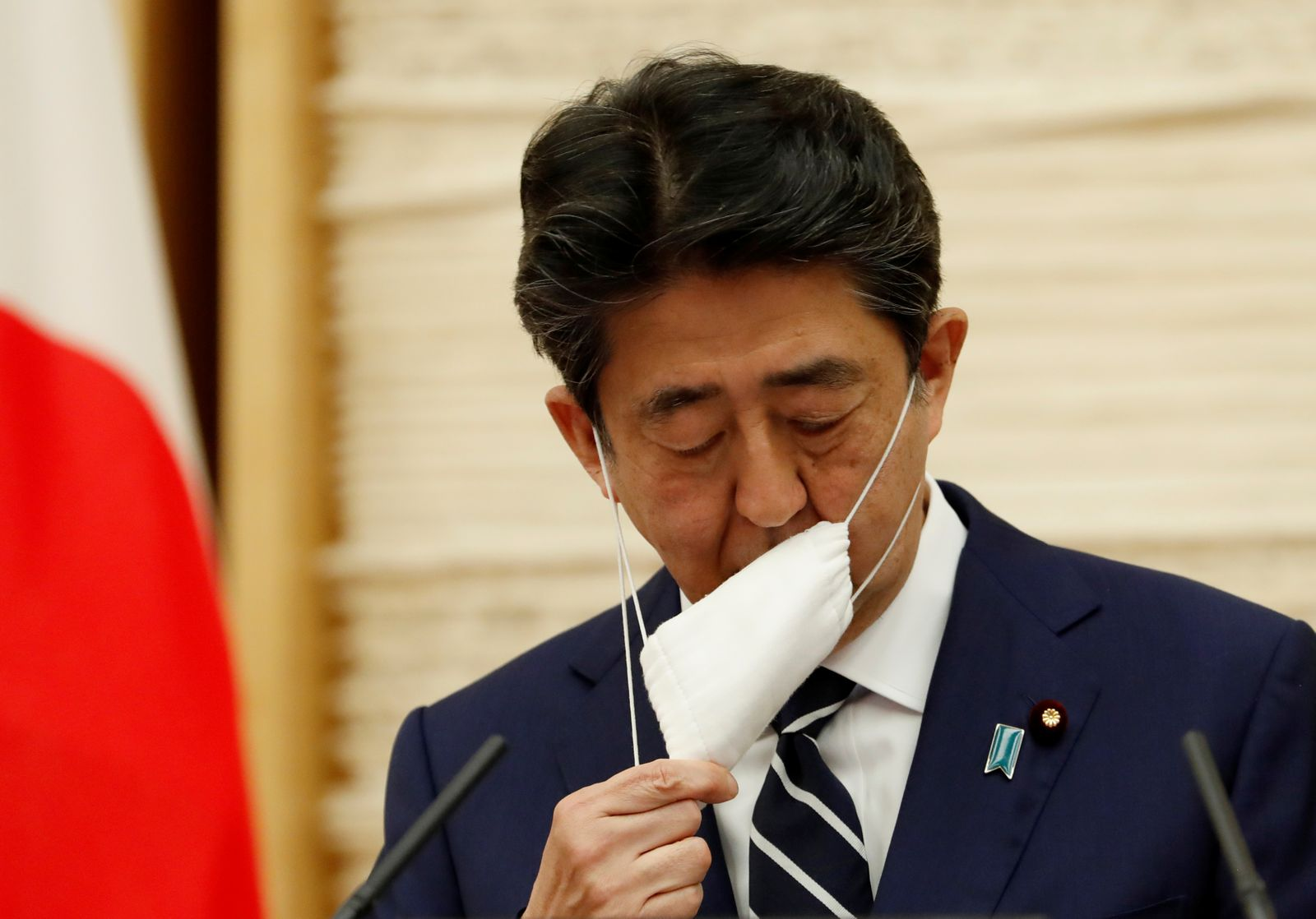 Japan's Prime Minister Shinzo Abe takes off his protective mask as he begins his news conference in Tokyo