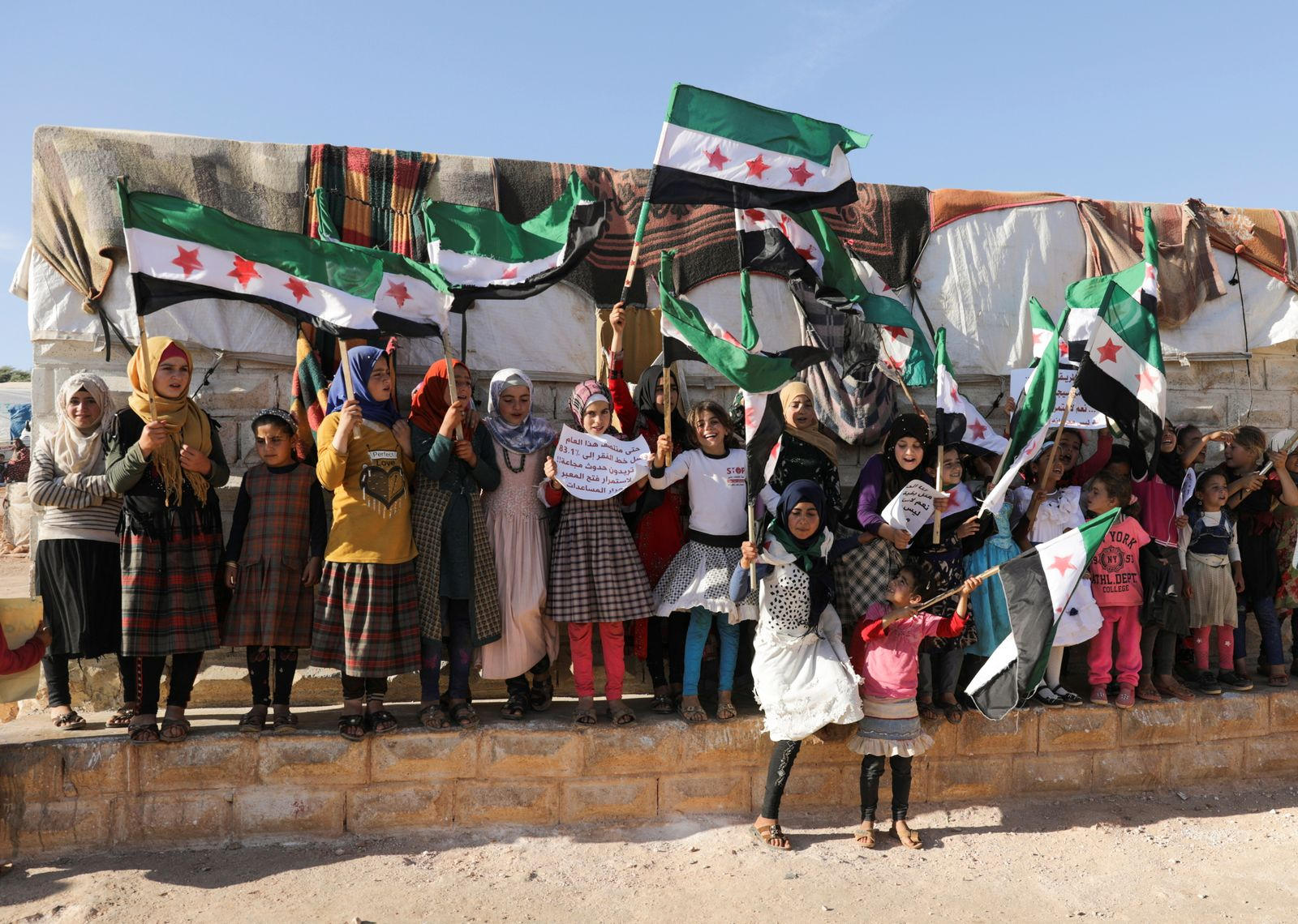 Internally displaced Syrian girls hold opposition flags during a protest against the closure of Bab al-Hawa crossing in the opposition-held Idlib