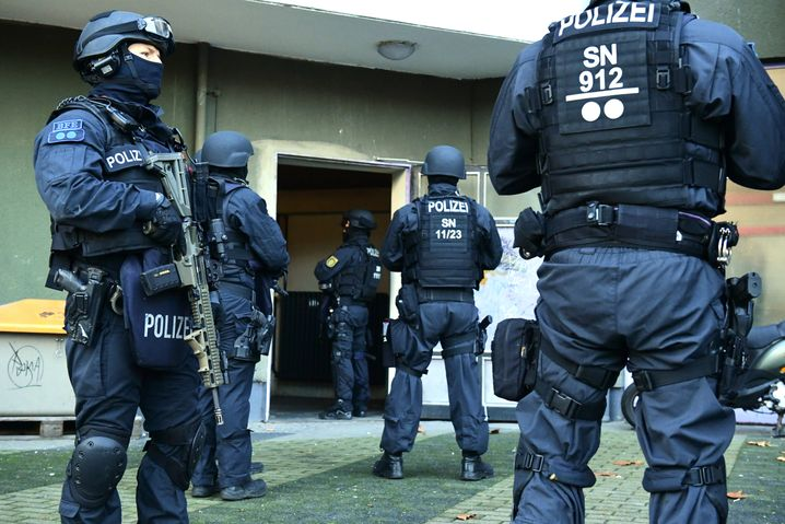 Schwer bewaffnete Polizisten sichern einen Hauseingang