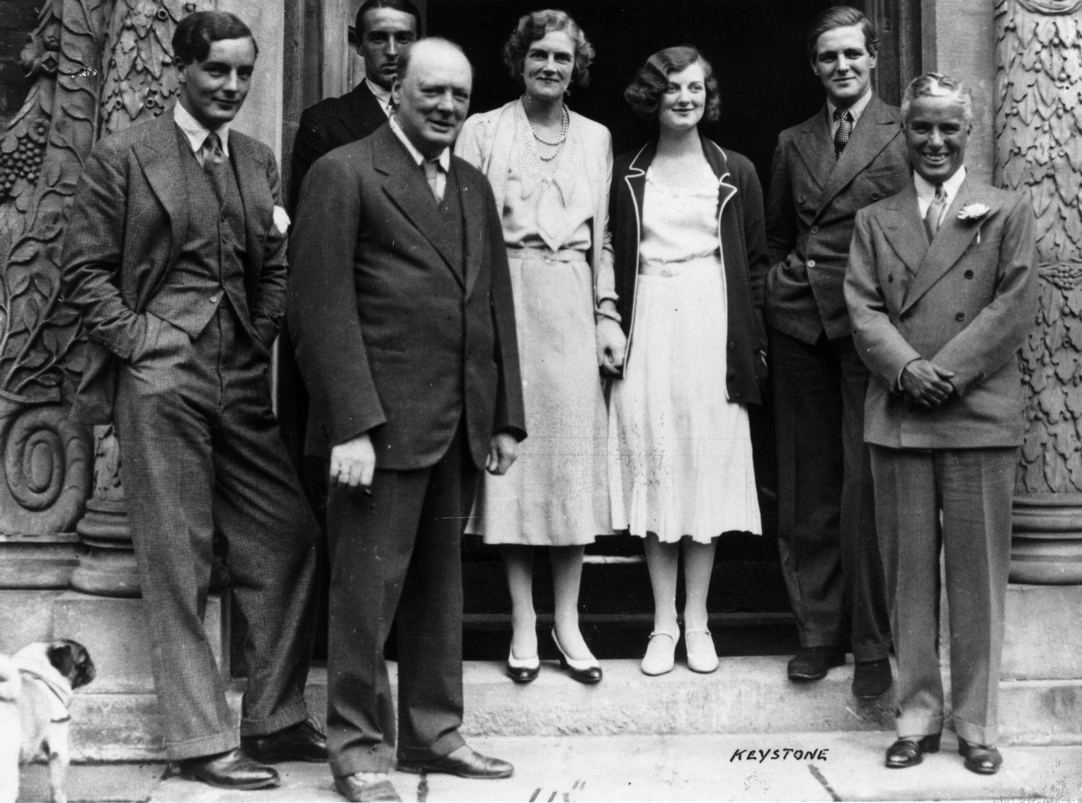 ЧЧерчилли: супружеская пара Уинстон и Клементина Черчилль (центр изображения) со своими детьми Дианой и Рэндольфом, а также актер Чарли Чаплин (р.) в июле 1931 года в Чартвелле. В крайнем левом углу стоит Том Митфорд, единственный брат сестер Митфорд, погибший в Бирме в 1945 году,-Клементина Черчилль была двоюродной сестрой Митфордов.