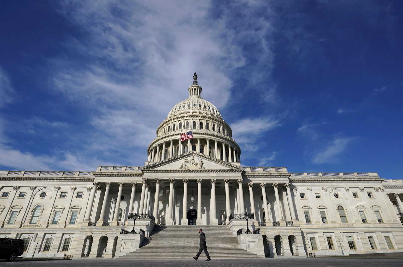 FILE PHOTO: FILE PHOTO: A man walks past the U.S. Capitol in Washington