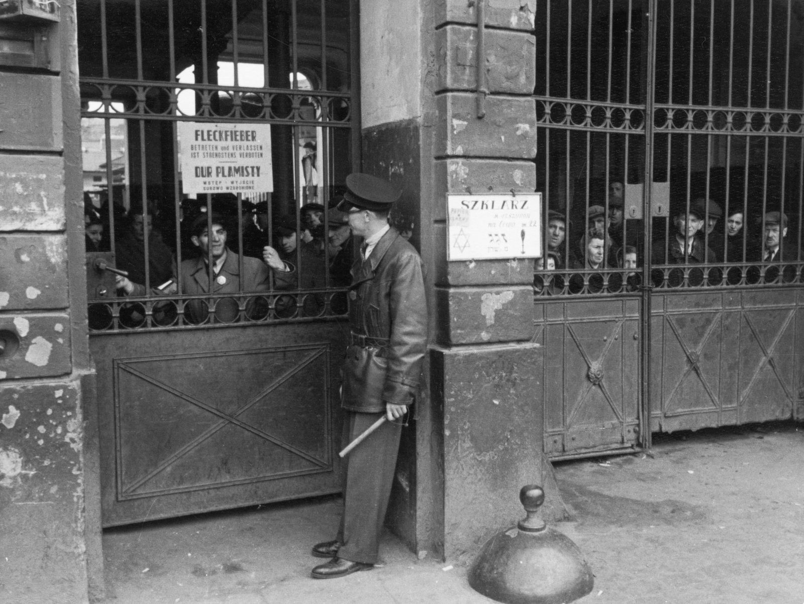 Fleckfieber-Warnung an einem Haus im Warschauer Ghetto, Angehörige der Ghettopolizei mit Schlagstock bewachen den Durchgang