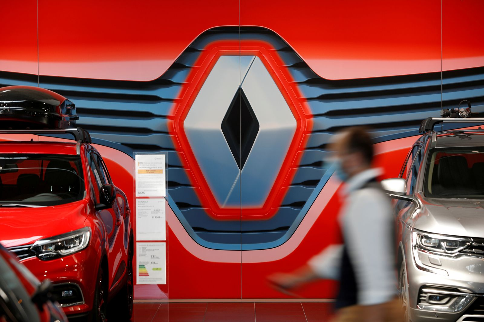 FILE PHOTO: An employee walks past a logo of Renault carmaker at a dealership in Nantes