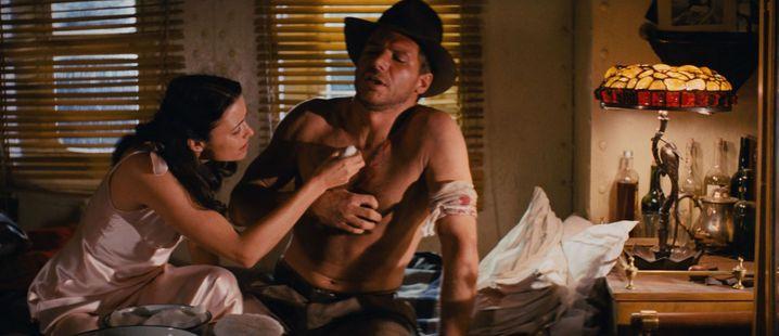 Tut's sehr weh? Rührend versorgt Marion Ravenwood (Karen Allen) den lädierten Indiana Jones (Harrison Ford).