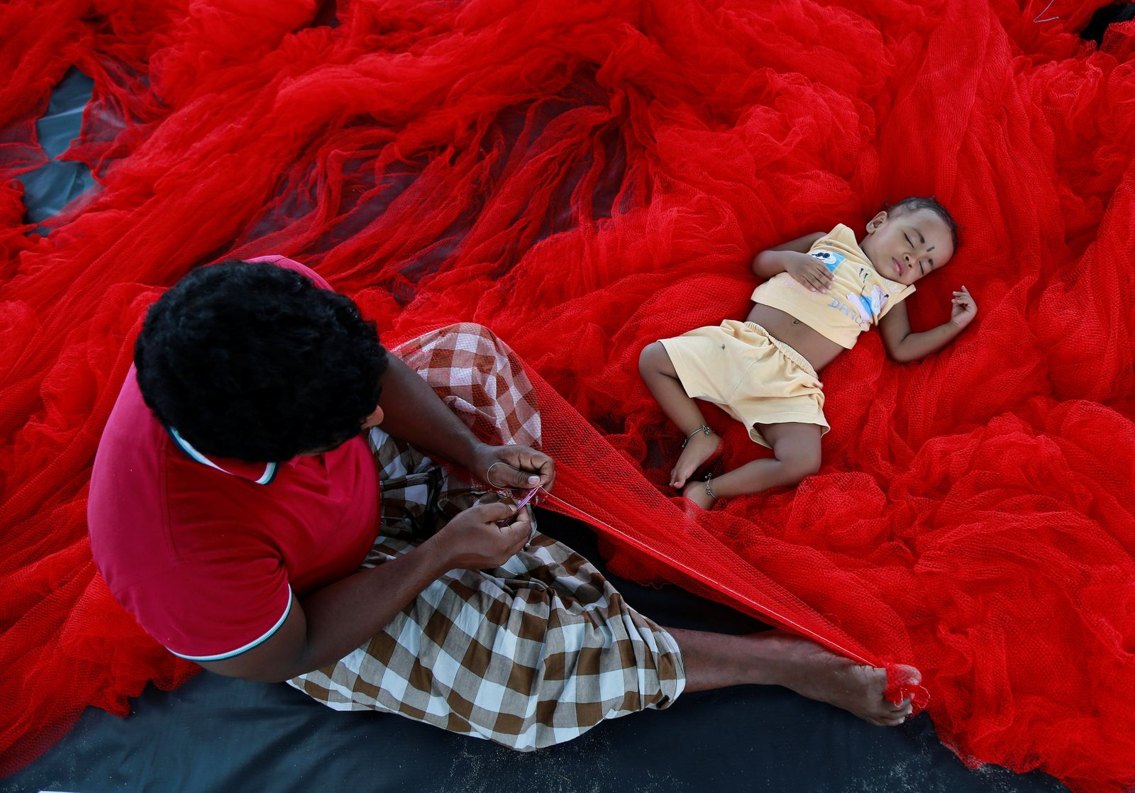 A fisherman stitches nets as his child sleeps beside him along the sea coast on the outskirts of Kochi