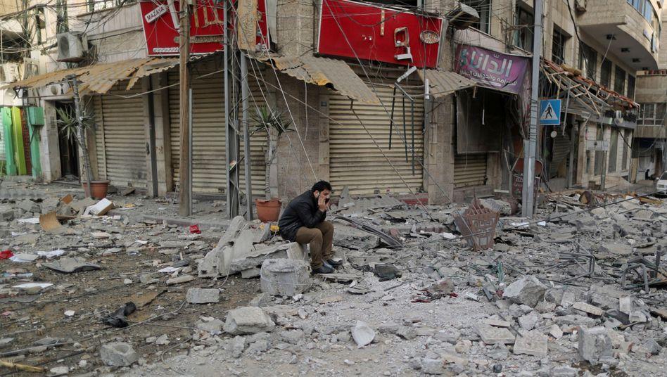 Palästinensischer Mann vor beschädigten Gebäuden in Gaza-Stadt