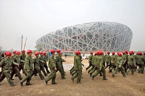 """Soldiers march next to the iconic National Stadium nicknamed the """"Bird Nest"""" under construction for the 2008 Beijing Olympic Games."""