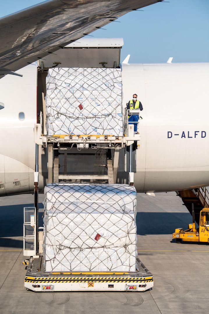 Schutzmasken werden aus einem Frachtflugzeug der Lufthansa ausgeladen