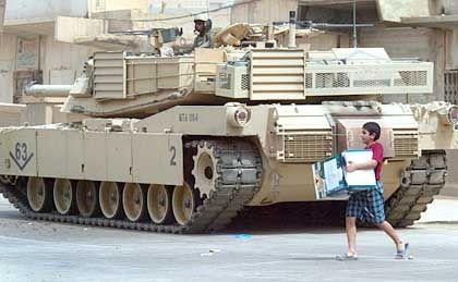 Plünderungen im Schatten von Panzern: Ein irakischer Junge bedient sich in einem Lagerhaus der Regierung in Bagdad