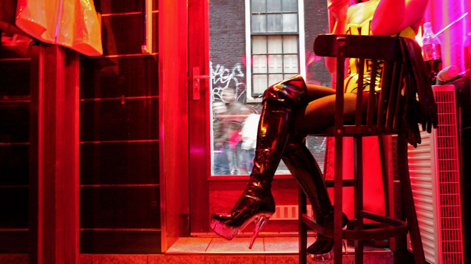 A German sex worker, who goes by the name Eve, sits at her workplace inside Amsterdam's red-light district.