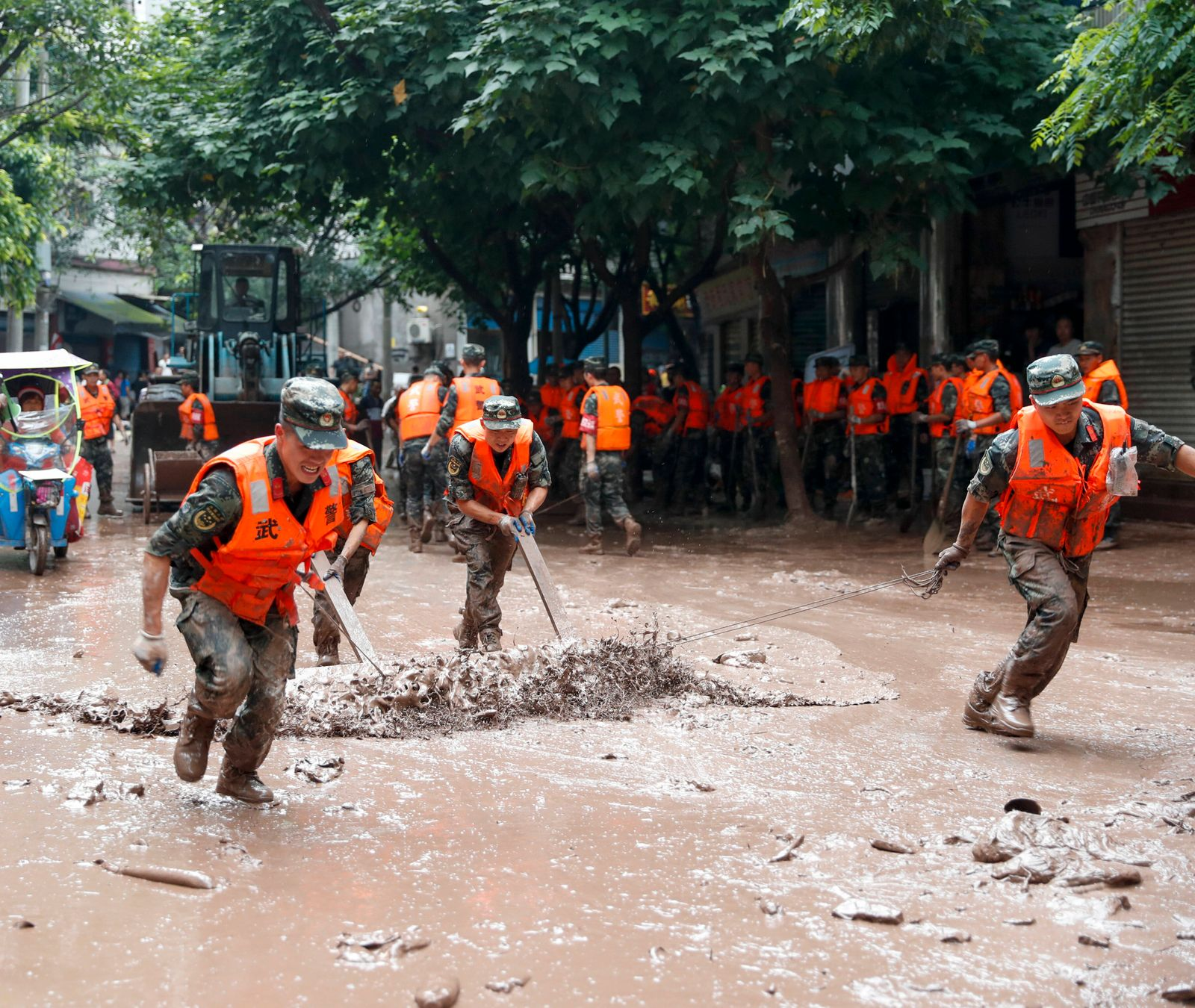 (200718) -- CHONGQING, July 18, 2020 -- Armed police clean the mud on the street in flood-hit Wuqiao subdistrict in Wan