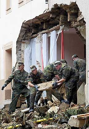 Bundeswehrsoldaten beseitigen am Mittwoch Trümmer eines durch die Hochwasserkatastrophe teilweise zerstörten Hauses in der sächsischen Kleinstadt Glashütte