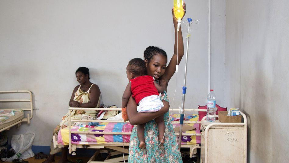 Eine Mutter hält ihr an Masern erkranktes Kind in einem Krankenhaus auf Madagaskar
