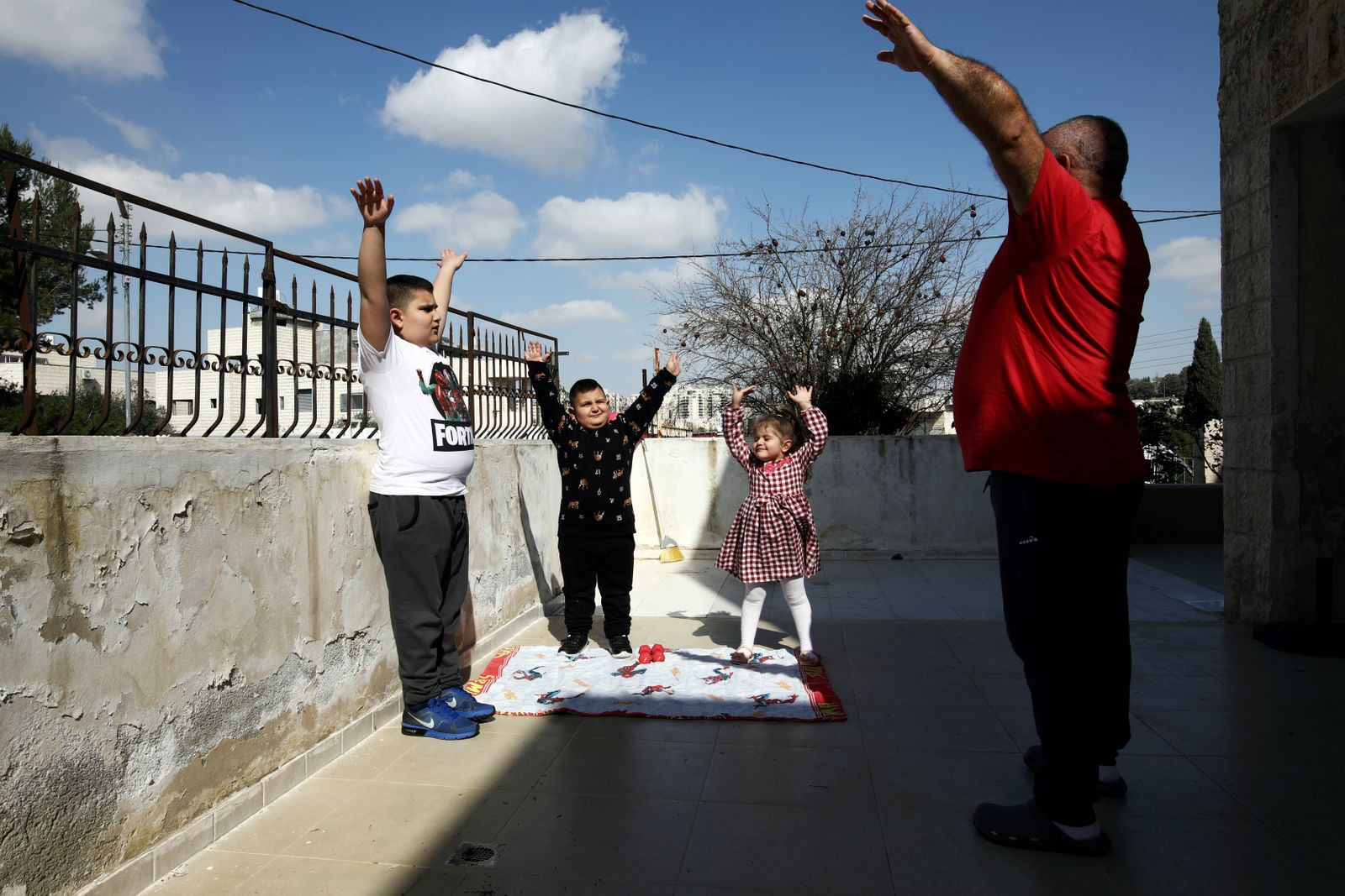Palestinian father Victor Anton Sara, 41, exercises with his children Anton, 11, Elie, 6, and Silva, 5, while observing a partial lockdown to curb the spread of the coronavirus disease (COVID-19) at their home in Jerusalem