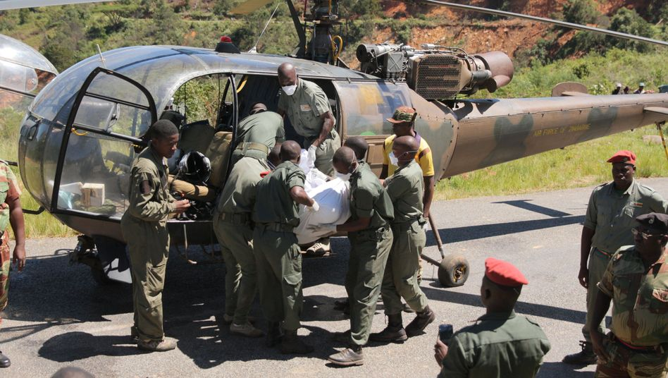 Einsatzkräfte in Simbabwe heben eine Leiche in einen Militärhubschrauber
