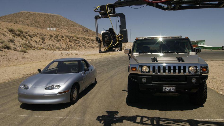 Zurück in die Zukunft: General Motors verspricht nach dem gescheiterten EV1 (links beim Dreh des Films »Who killed the electric car?«, deutsch: »Warum das Elektroauto sterben musste«) ein zweites Mal, aufs Elektroauto zu setzen – elektrifiziert diesmal aber den Geländewagen Hummer (rechts eine zeitgenössische Version)