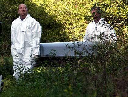 Polizisten tragen den Sarg mit der Leiche von Jakob von Metzler vom Fundort bei Schlüchtern weg