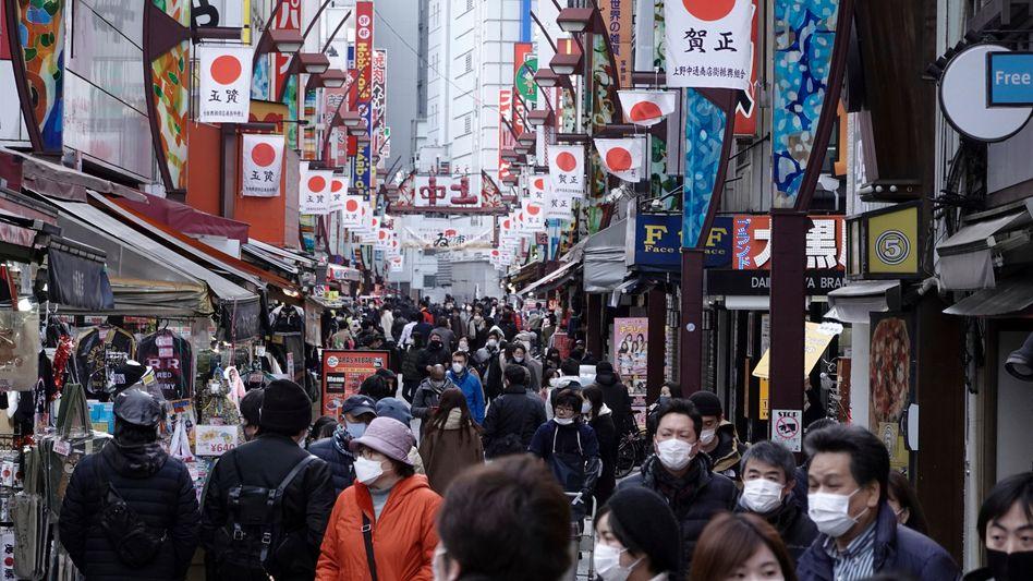 Zahlreiche Passanten mit Mund-Nasen-Schutz gehen eine Einkaufsstraße in Tokios Stadtteil Ueno entlang